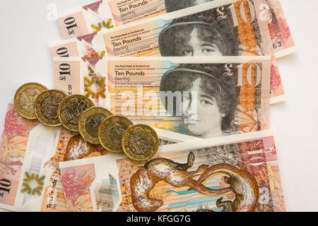 Close up of Royal Bank of Scotland new plastic polymer ten pounds £10 banknote and new hexagonal one pound £1 coins, - Stock Photo