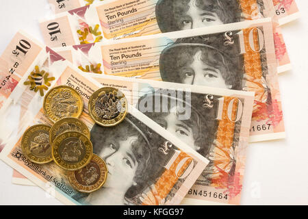 Close up of Royal Bank of Scotland new plastic polymer ten pounds £10 banknote and new hexagonal one pound £1 coins - Stock Photo