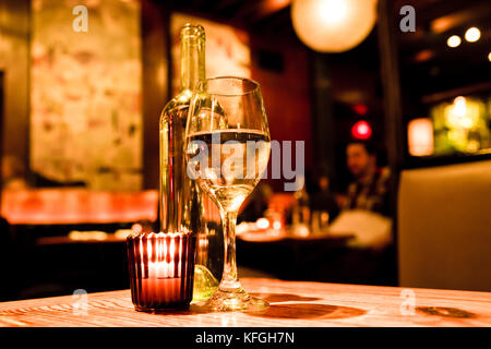 Wine glass, bottle and candle on table in restaurant with warm light - Stock Photo