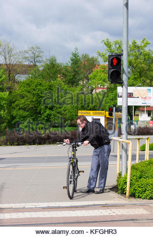 POZNAN, POLAND - MAY 04, 2014: Man with bicycle waiting in red light in front of a zebra crossing - Stock Photo