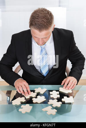 Businessman solving a jigsaw puzzle at his desk sitting down with the pieces spread out in front of him  conceptual - Stock Photo