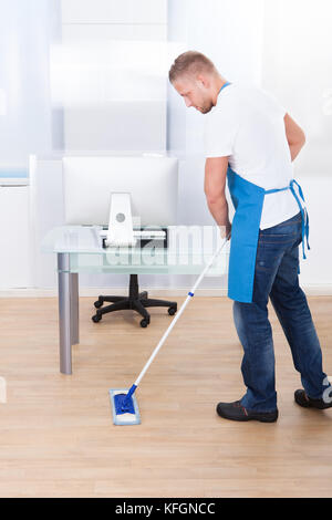 Handsome male janitor or cleaner cleaning the floor in an office building using a mop to wash the and disinfect - Stock Photo
