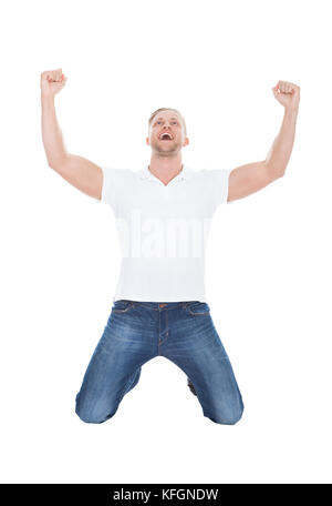 Excited man cheering in jubilation dropping down on his knees with his fists raised in the air as he celebrates - Stock Photo