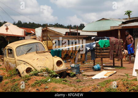 Nigerian man outdoors with an old car and hanging clothes, in a poor suburb of the large city of Lagos, Nigeria - Stock Photo