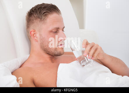 Man lying in bed propped up against the pillows drinking a glass of fresh water - Stock Photo