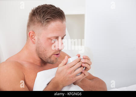 Man lying in bed propped up against the pillows drinking a cup of hot tea - Stock Photo