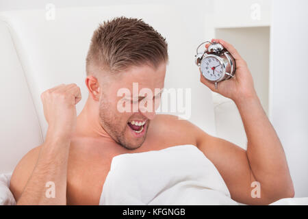 Man screaming in frustration at his alarm clock as it wakes him up after a sleepless night - Stock Photo