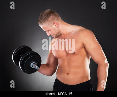 Muscular shirtless young man lifting weights in a gym as he works out during a training or body building session - Stock Photo