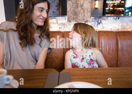 Funny tender scene. Four years age blonde happy girl sticking her tongue out to smiling woman mother sitting in - Stock Photo