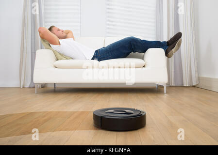 Man Relaxing On Sofa With Robotic Vacuum Cleaner On Hardwood Floor - Stock Photo
