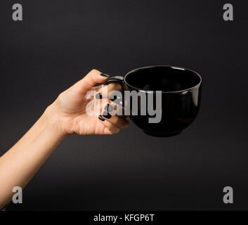 Black, steaming mug, price-tag in front of it. Grey background. - Stock Photo