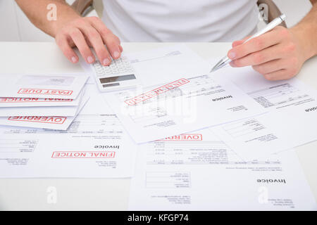 Close-up Of A Man Calculating Unpaid Bills Using Calculator - Stock Photo