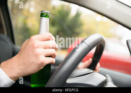Close-up Of A Man's Hand In Car Holding Beer Bottle While Driving - Stock Photo