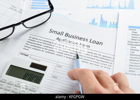 Hand With Pen And Calculator On Business Loan Application Form - Stock Photo