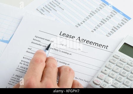 Close-up Of Person Hand With Pen And Calculator Over Lease Agreement - Stock Photo