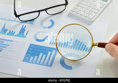 Close-up Of Person's Hand Holding Magnifying Glass Over Graph - Stock Photo