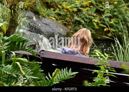A young woman sitting on a bench thinking with her back to camera next to a waterfall or water feature in a beautiful - Stock Photo
