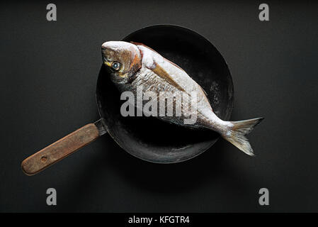 Delicious fresh fish on dark vintage background. Healthy food, diet or cooking concept - Stock Photo