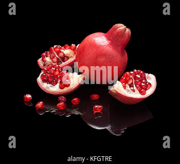 Pomegranate fruit with seeds and slices isolated on black glossy background with real reflection. - Stock Photo