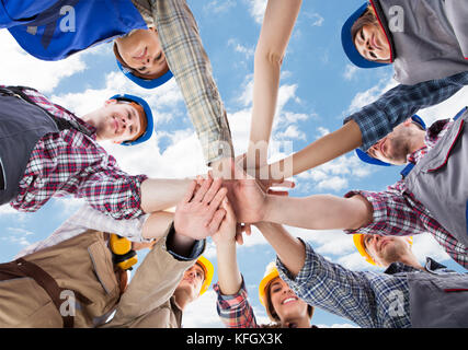 Directly below shot of multiethnic architects piling hands against sky - Stock Photo