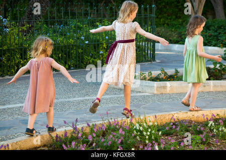 Three young sisters / girls / children / kids / kid aged 7, 3, & 5 years, on family holiday balance, run, & play - Stock Photo