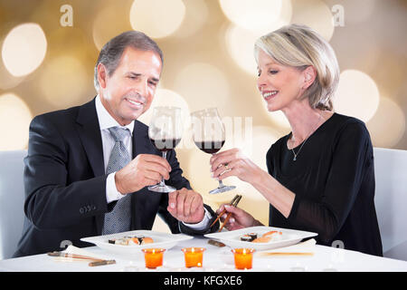Happy couple toasting wineglasses while having dinner at restaurant table - Stock Photo