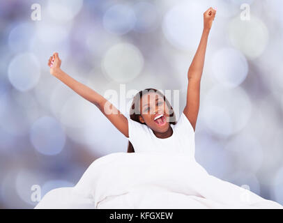 Portrait of young woman yawning while stretching in bed - Stock Photo