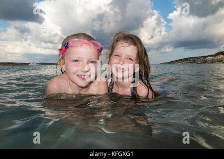 Sisters aged seven and five years old swim and play at Mellieha bay beach on the north coast of the main island - Stock Photo