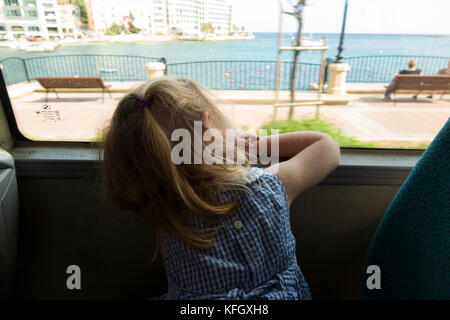 Three year old girl / child / passenger / passengers travelling on a public bus / using public transport in St Julians - Stock Photo