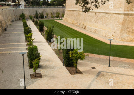 The Mdina Ditch Garden with well cared for perfect lawn grass and which surrounds much of the walled city of Mdina - Stock Photo