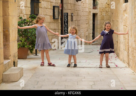 Three young sisters / girls / children / kids / kid aged 7, 3, & 5 years old, on a family holiday, run & play and - Stock Photo