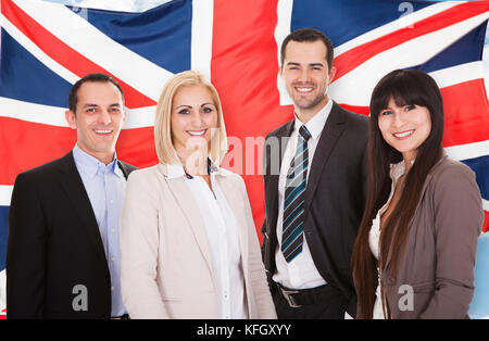 Group Of Happy Businesspeople Standing In Front Of British Flag - Stock Photo