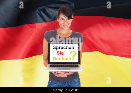 Young Woman Holding Laptop Asking Do You Speak German - Stock Photo