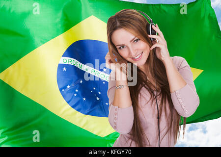 Woman Listening Brazilian Language Learning Audiobook On Headphones In Front Of Brazilian Flag - Stock Photo