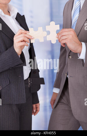Midsection of businessman and businesswoman joining jigsaw pieces in office - Stock Photo