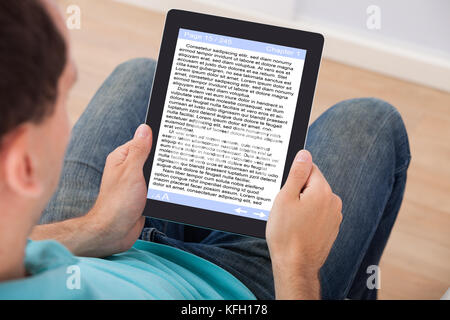 Man reading eBook on digital tablet at home - Stock Photo