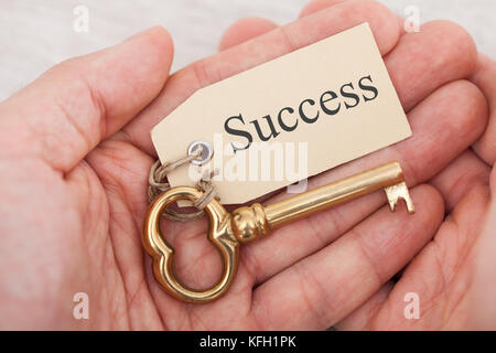 Closeup of man holding golden key with success tag - Stock Photo