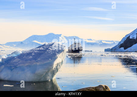 Blue antarctic cruise vessel among the icebergs with glacier in background, Neco bay, Antarctica - Stock Photo