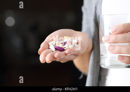 Close up of a woman hand holding a lot of pills and a glass of water with a dark background - Stock Photo