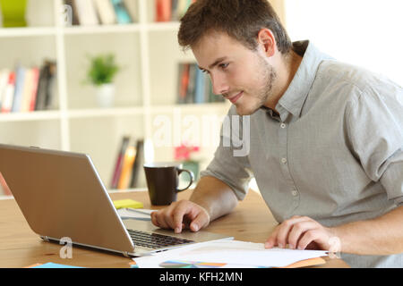 Serious freelancer working checking on line content in a laptop on a desk at home - Stock Photo