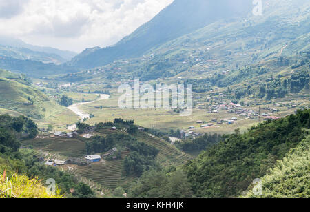 landscape view of village in valley near the mountains and rice terraces with cloudy SaPa, Vietnam - Stock Photo