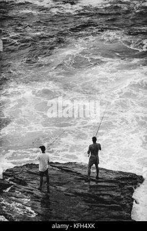 Two men stand on a rock in rough water fishing along the Bondi to Coogee coastal walk in Sydney, Australia. - Stock Photo