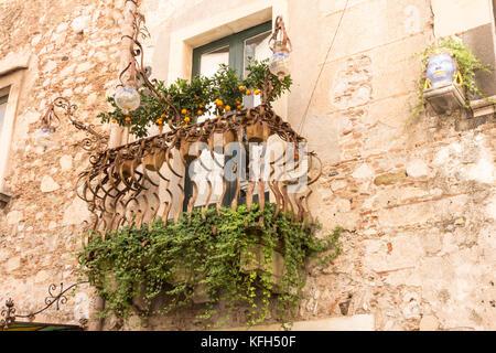 Wrought iron balcony with pots of kumquats, Taormina, Sicily, Italy - Stock Photo