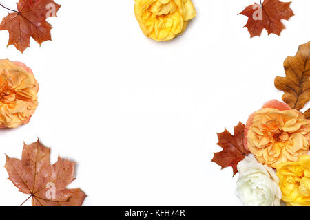 Autumn floral frame made of colorful maple and oak leaves and fading apricot and yellow roses isolated on white - Stock Photo