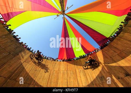 A dare devil motorbike show where the biker takes life risk running his bike along the wall of a large wooden well - Stock Photo