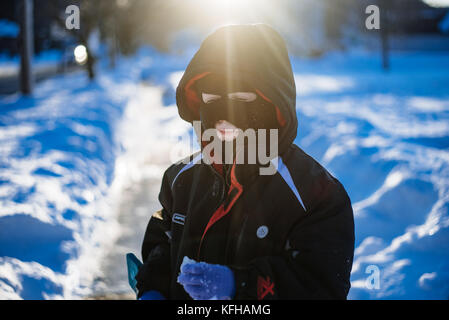 10-11 year old boy standing in snow with ski mask - Stock Photo