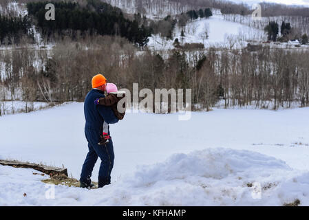 Man holding infant in winter with snow - Stock Photo