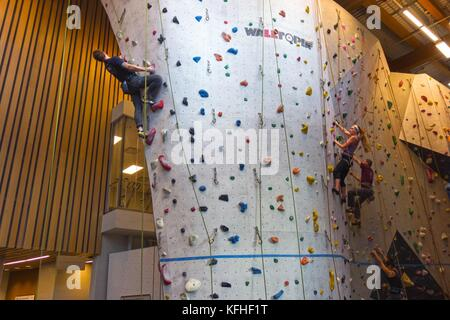 Climbers Scaling Vertical Rock Climbing Wall in Elevation Place Recreation Facility in Canmore Alberta - Stock Photo