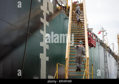 Two workers go up the ladder aboard the ship under construction. Cam Rahn shipyard, Vietnam. - Stock Photo