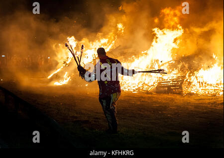 Bonfire Night Celebrations In West Sussex. With hot embers in the air, a bonfire society member struggles against - Stock Photo